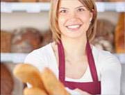 Fröhliche Bäckerin hält Baguettes in der Hand.