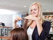 Friseurin schneidet entspannt die Haare.